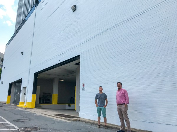 Artist Jason Jones with DLRP Executive Director Gabe Holmstrom standing in front of location of future mural